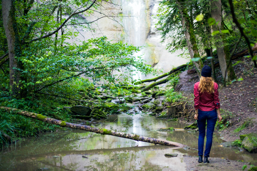 Woman in park looking at beautiful waterfall.